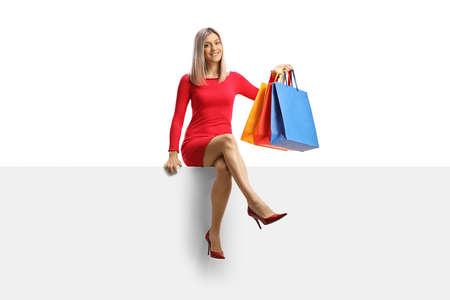Blond woman in a red dress sitting on a panel with shopping bags isolated on white background