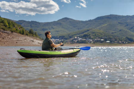 Fisherman in a canoe on a lake surrounded by mountains on a sunny day 스톡 콘텐츠