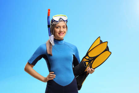 Woman with a snorkeling equipment, mask and fins, on a blue sky