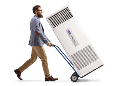 Full length profile shot of a bearded man pushing a hand-truck with a portable self standing ac unit isolated on white background