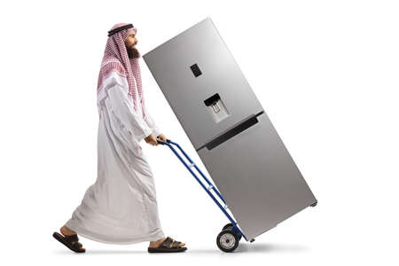 Full length profile shot of a saudi arab man pushing a hand truck with a fridge isolated on white background