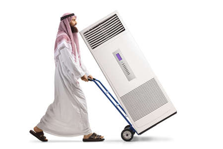 Full length profile shot of a saudi arab man pushing a hand truck with a self standing AC unit isolated on white background