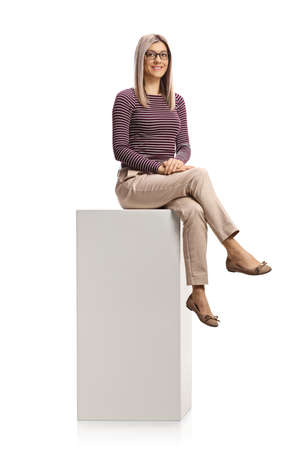Young woman with glasses sitting on a white column isolated on white background Banque d'images