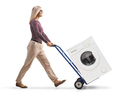 Full length profile shot of a young woman pushing a washing machine with a hand-truck isolated on white background
