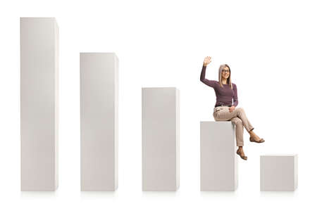 Young blond woman with glasses sitting on a white graph chart and waving isolated on white background