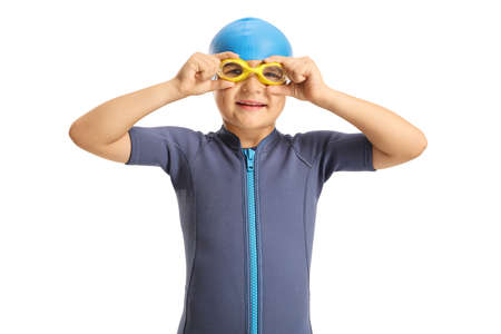Boy in a wetsuit putting on swimming goggles isolated on white background