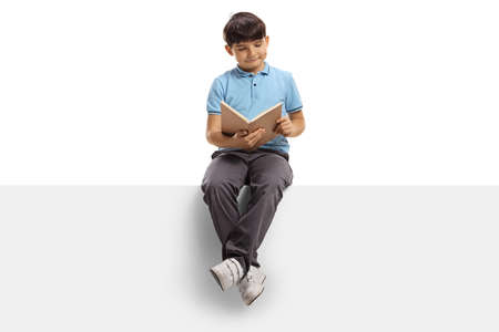 Boy sitting on a blank panel and reading a book isolated on white background