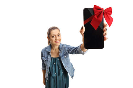 Happy young woman holding a smartphone with red ribbon bow isolated on white background