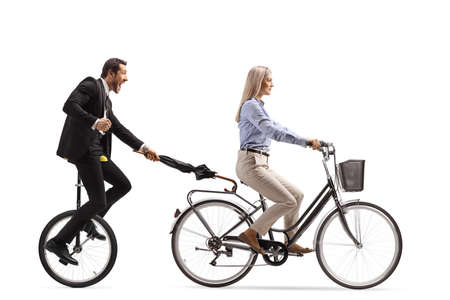 Man in a suit and tie holding an umbrella and riding a tricycle behind a woman on a bicycle isolated on white background