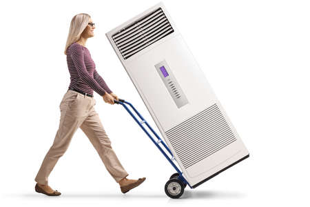 Full length profile shot of a woman pushing a hand-truck with a self standing ac unit device isolated on white background