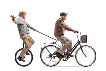 Elderly man riding a bicycle and pulling another man with a tricycle and walking cane isolated on white background 스톡 콘텐츠