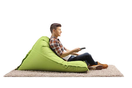 Guy sitting on a green bean bag armchair and holding a remote control isolated on white background