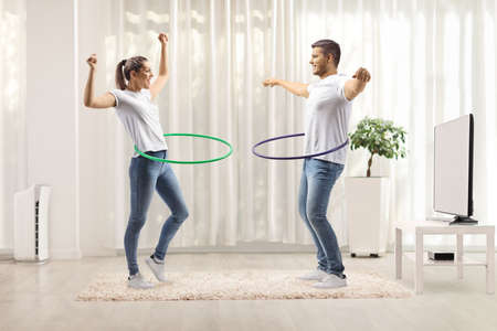 Young ccheerful couple spinning hula hoops at home in a living room