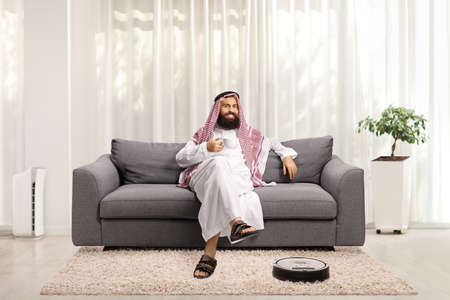 Saudi arab man at home resting on s sofa and a robotic vacuum cleaner cleaning the floor