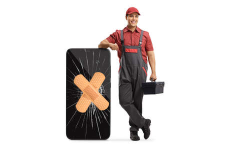 Mobile phone repair technician leaning on a smartphone with a broken screen and aid isolated on white background