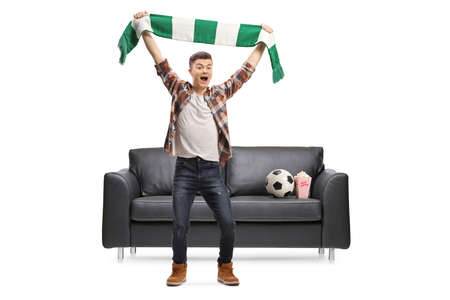 Full length portrait of a male teenager cheering with a scarf in front of a sofa with a soccer ball and popcorn isolated on white background