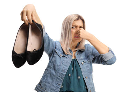 Young woman holding a pair of smelly shoes isolated on white background