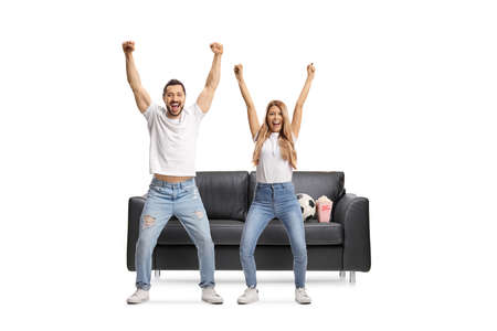 Full length portrait of a young man and woman watching football and cheering isolated on white background
