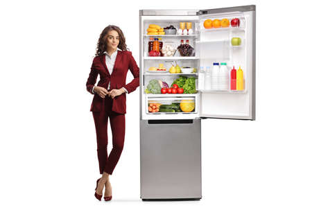 Full length portrait of a young professional woman leaning on an open fridge isolated on white background