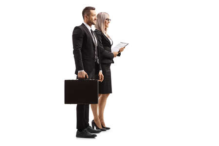 Full length profile shot of a professional man and woman with a briefcase and a clipboard isolated on white background Banque d'images
