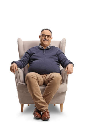 Happy mature man sitting in an armchair and smiling isolated on white background Banco de Imagens