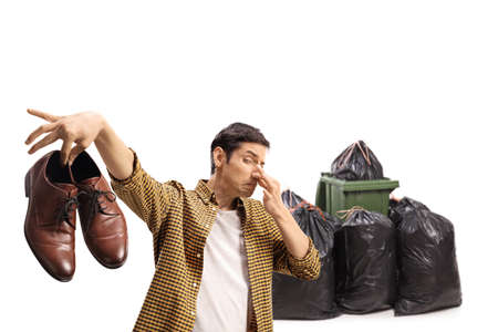 Man throwing a pair of smelly shoes in the garbage isolated on white background