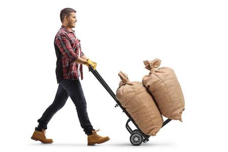 Man pushing burlap sacks on a hand truck isolated on white background