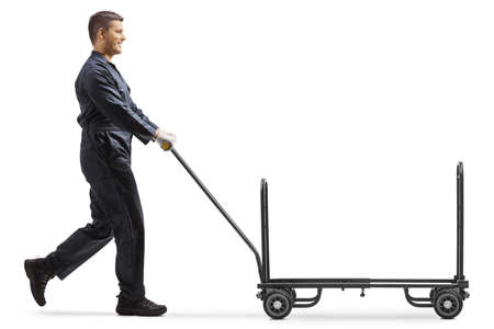 Worker in a uniform pushing an empty hand truck isolated on white background