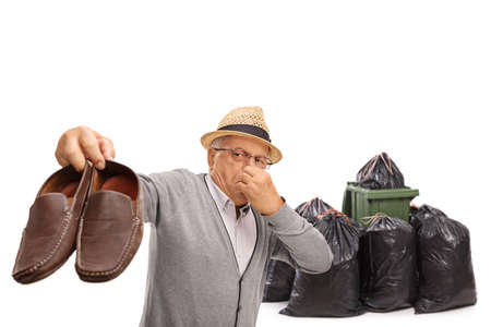 Elderly man holding a pair of stinky shoes near a waste bin and bags isolated on white background