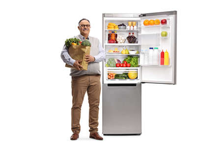 Full length portrait of a mature man with a grocery bag standing next to an open full fridge isolated on white background