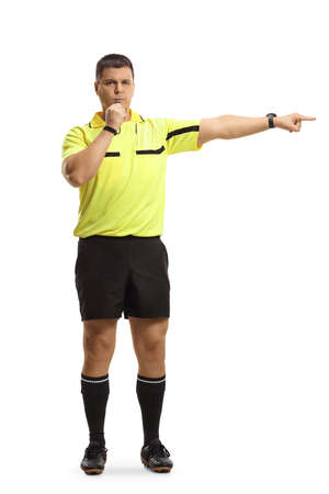 Full length portrait of a football referee blowing a whistle and pointing with finger isolated on white background