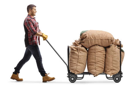 Male agricultural worker pushing a hand truck with burlap sacks isolated on white background
