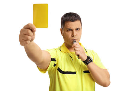 Football referee blowing a whistle and showing a yellow card isolated on white background Stockfoto