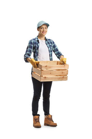 Full length portrait of a female farmer worker carrying an empty crate isolated on white background Imagens