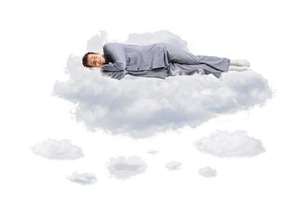 Young man in pajamas floating in the air and sleeping on clouds isolated on white background Imagens