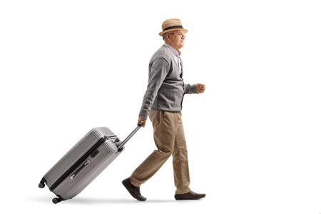 Full length profile shot of an elderly man walking and pulling a suitcase isolated on white background