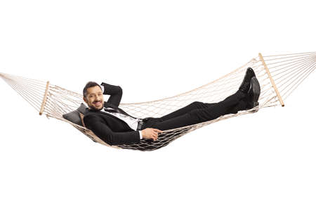 Happy young businessman lying on a hammock swing isolated on white background Stockfoto
