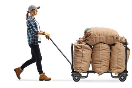 Female farmer worker pushing a hand truck with burlap sacks isolated on white background