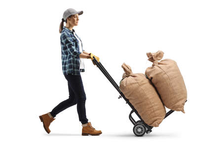 Full length profile shot of a female farmer pushing a hand truck with burlap sacks isolated on white background