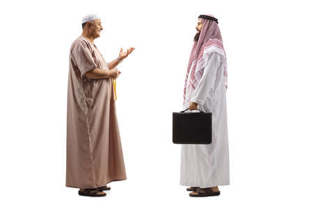 Full length profile shot of a mullah talking to a saudi arab businessman isolated on white background