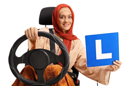 Young muslim woman in a car seat holding a learner plate