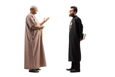 Full length profile shot of a muslim man in traditional clothes talking to a christian priest Stock Photo