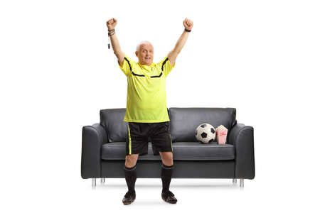 Football referee standing in front of a couch and cheering with hands up isolated on white background