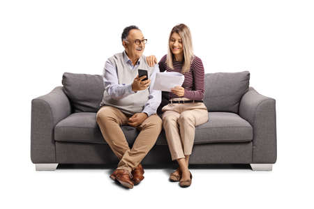 Young woman and a mature man sitting on a sofa with a mobile phone and a paper document isolated on white background