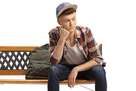 Pensive male student sitting on a bench and looking away isolated on white background