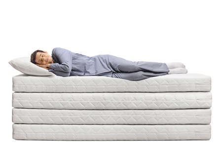 Full length shot of a young man sleeping peacefully on a pile of soft mattresses isolated on white background