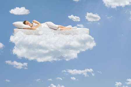 Young woman sleeping on a floating mattress up in the clouds and a blue sky