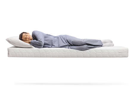 Full length shot of a man in pajamas sleeping peacefully on a floating mattress isolated on white background Standard-Bild