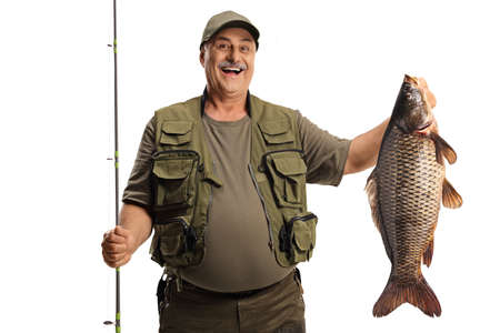 Happy fisherman holding a big carp fish and smiling isolated on white background