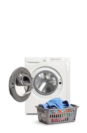 Studio shot of an emptied washing machine and a laundry basket isolated on white background